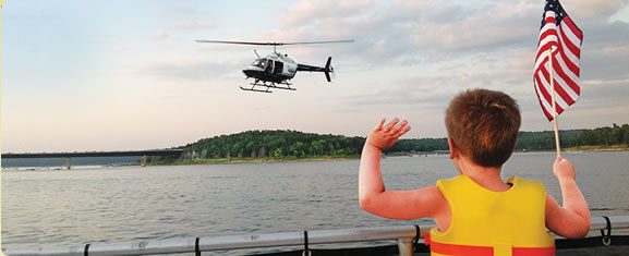 Image of a child holding the american flag waving to a helicopter over a lake.